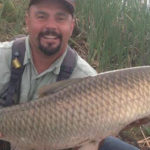 Mike Medina holding a 30 pound Colorado grass carp with a big smile.