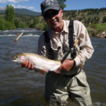 Happy fly fisherman showing his catch while wading in stream