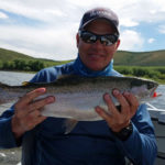 Chris Galvin holding a large rainbow trout caught fly fishing from a drift boat loch style