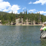 Boy holding bent fly fishing rod wading in a trout lake with scenic mountain view