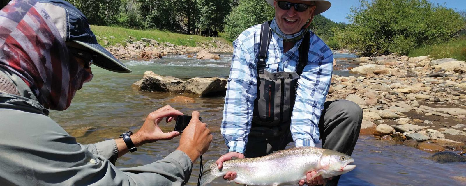 One man taking a picture of another man who is holding a trophy sized trout along the banks of the North Fork of the South Platte, near Bailey.