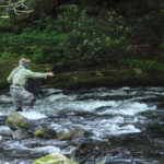 Chris Galvin stands in swift water with fly rod pointed upstream