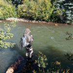 Teen angler stands perched on streamside rock with bent fly fishing rod over green tinted river.