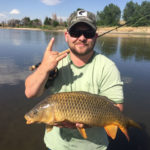 An angler on the South Platte River holding a large common carp caught on the fly.