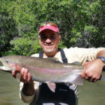 Fisherman hoisting a big rainbow trout from a private ranch near Bailey Colorado.